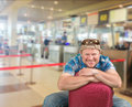 Tourist man sitting with suitcase at airport Royalty Free Stock Photo