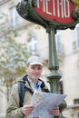 Tourist with a map in paris france under the sign of metro Stock Photo