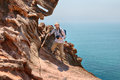 Tourist photographer climbs the cliff above sea, Hormuz Island,