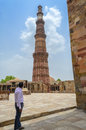 Tourist photographing old ancient building or structure a taking photograph with his smart mobile phone of qutub minar the Royalty Free Stock Images