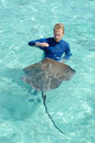 Tourist playing with stingray in a lagoon and feeding himantura fai the shallow clear water of the of bora bora an island the Royalty Free Stock Image