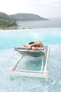 Tourist sleep on deckchair and swimming pool Royalty Free Stock Photo