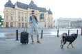 Tourist takes picture to a stray dog young with camera and suitcase pictures in bucharest Royalty Free Stock Photo
