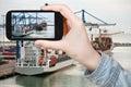 Tourist taking photo of copenhagen cargo seaport travel concept on mobile gadget at sunrise Stock Photo