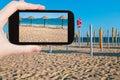 Tourist taking photo of straw beach umbrellas travel concept on ocean coast portugal algarve on mobile gadget Royalty Free Stock Photos
