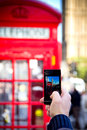 Tourist taking a picture in london holds up camera mobile at red phone booth and big ben Royalty Free Stock Image