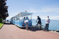 Tourist train blue and children riding behind him on bicycles quay in the city even Stock Image