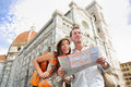 Tourist travel couple by florence cathedral italy looking at map in front of il duomo di firenze also called basilica di santa Stock Photo