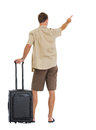 Tourist with wheels bag pointing on copy space Stock Images