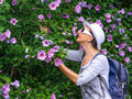 Tourist woman with flowers hibiscus syriacus white hat and sun glasses studying in park or garden Royalty Free Stock Photos