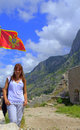 Tourist woman hiking in old montenegro fortress flag waving and sightseeing the medieval kotor ruins against picturesque mountain Stock Image