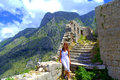 Tourist woman hiking in old montenegro fortress sightseeing the medieval kotor ruins against picturesque mountain ridges and nice Royalty Free Stock Photos