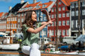 Tourist woman at the Nyhavn harbor pier Copenhagen, Denmark. Royalty Free Stock Photo
