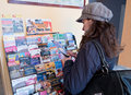 Tourist woman in paris reading travel brochures and flyers displayed in promotional advertising stand Stock Photos