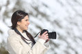 Tourist woman photographing on winter holidays with a snowy mountain in the background Royalty Free Stock Photo