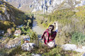 Tourist woman sitting on the top of the  autumn mountain taking photos with the phone Royalty Free Stock Photo