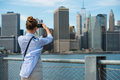 Tourist woman taking travel picture with camera of Manhattan Skyline and New York City skyline during autumn holidays. Royalty Free Stock Photo