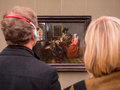 Tourists admire a paint in a gallery Royalty Free Stock Photo