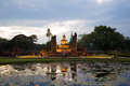 Tourists at the ancient sculpture of seated Buddha in the evening twilight. Historical Park of Sukhothai, Thailand