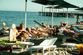 Tourists on the beach sunbathing swimming resting to sea turkey beldibi hotel with sun beds and umbrellas Stock Image