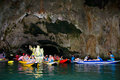 Tourists in boat swim into the cave of the island.