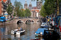 Tourists on canal boat in amsterdam view of bridge and traditional buildings Stock Images