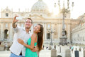 Tourists couple by vatican city in rome and st peter s basilica church happy travel women and men taking selfie photo picture on Stock Photo