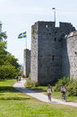 Tourists and cyclists at towers in the medieval city wall of visby swedish visby ringmur the hanseatic city of visby is listed as Stock Image