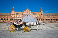 Tourists enjoy a trip on horsedrawn cart on plaza de espana sev seville was built in is huge half circle with total Stock Photos