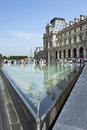 Tourists enjoy the view and water basin at Louvre Museum, Paris