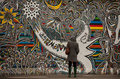Tourists examine graffiti on Berlin wall Stock Photography