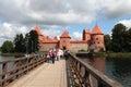 Tourists on the lake bridge with Trakai Castle, Lithuania Royalty Free Stock Photo
