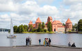 Tourists on the lake coast with Trakai Castle, Lithuania Royalty Free Stock Photo