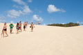 Tourists at lake wabby sand blow fraser island queensland australia walk across the desert like in march Stock Image