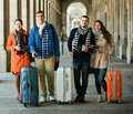 Tourists with luggage walking by street two couples of young smiling travelers in the city Stock Images