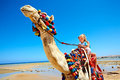 Tourists riding camel on the beach of egypt children sharpness a Royalty Free Stock Images