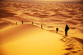 Tourists in sahara climbing the dunes early morning desert morocco Royalty Free Stock Image