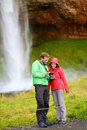 Tourists with slr camera by waterfall on iceland romantic couple visiting famous tourist attractions and landmarks in icelandic Royalty Free Stock Photography