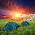 Tourists tents on mountain s meadow against sunset background Stock Images