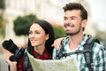 Tourists two happy young with backpacks touristic map and camera sightseeing city Royalty Free Stock Images