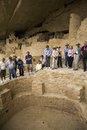 Tourists viewing kiva at Cliff Palace cliff Stock Images