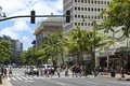 Tourists in waikiki hawaii june walk across kalakaua avenue on june is oahus main hotel and resort area and a Royalty Free Stock Image