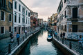Tourists walk alongside a canal in Venice at dusk. Royalty Free Stock Photo