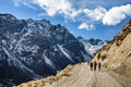 Tourists walk to black mountain with snow on the top and yellow stone ground at Thangu and Chopta valley in winter in Lachen Royalty Free Stock Photo