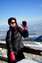 Tourists woman enjoying the winter mountain view and waving for goodbye young smiling in a beautiful blue sky Royalty Free Stock Photo
