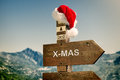Towards christmas signpost with santa hat against a mountain landscape Royalty Free Stock Images