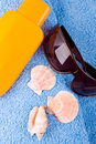 Towel, shells, sunglasses and lotion Royalty Free Stock Photo