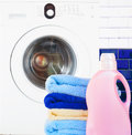 Towels with detergent and washing machine pile of in bathroom Stock Image