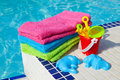 Towels and plastic toys near the swim pool Stock Photos