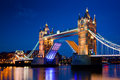 Tower bridge in london the uk at night is opening Royalty Free Stock Photo